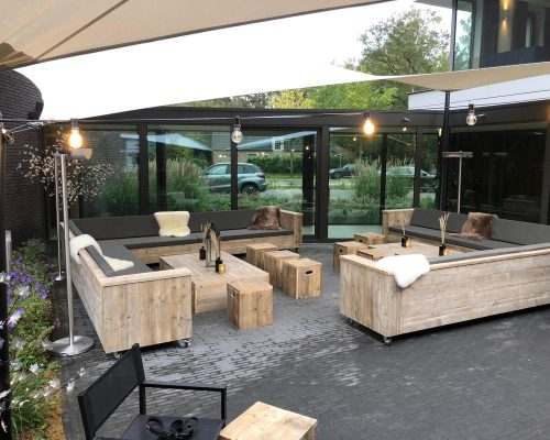 Meubelen van steigerhout voor buitenterras van het hotel